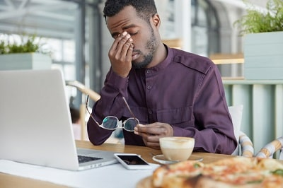overworked-professional-male-economist-holds-spectacles-being-tired-to-work-at-laptop-computer-much-hours-has-he-min