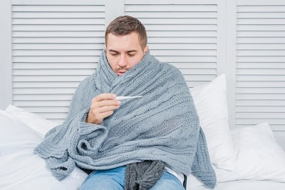 sick-man-wrapped-in-shawl-looking-at-thermometer-min