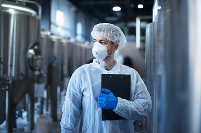 technologist-in-protective-white-suit-with-hairnet-and-mask-standing-in-food-factory-min
