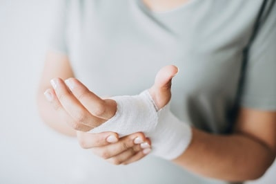 woman-with-gauze-bandage-wrapped-around-her-hand-min