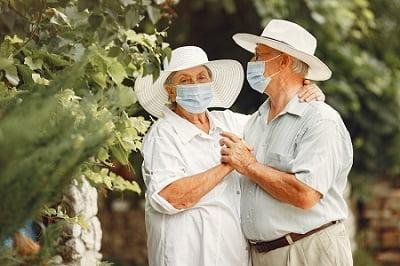 adult-couple-in-summer-garden-coromavirus-theme-people-in-medical-mask-handsome-senior-in-white-shirt-min