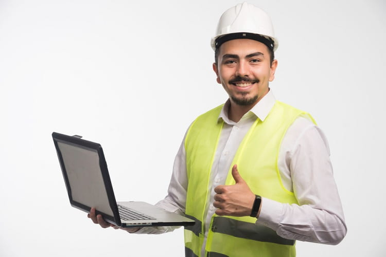 engineer-in-uniform-holding-laptop-and-making-thumb-up-min