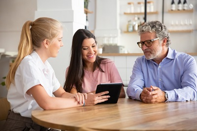 female-agent-or-manager-meeting-with-couple-of-young-and-mature-customers-presenting-content-on-tablet