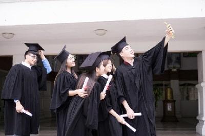 graduandose-al-aire-libre-diploma-educacion-bachiller-min