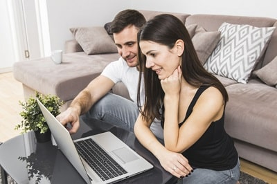 pareja-joven-sonriente-usando-laptop-casa