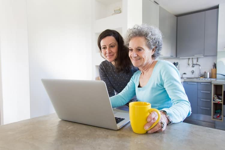 positive-senior-lady-showing-photos-to-daughter-on-laptop-min