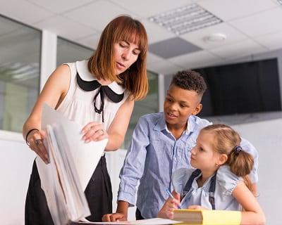 teacher-showing-her-students-their-grades-min