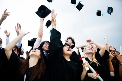 group-of-diverse-grads-throwing-caps-up-in-the-sky-min