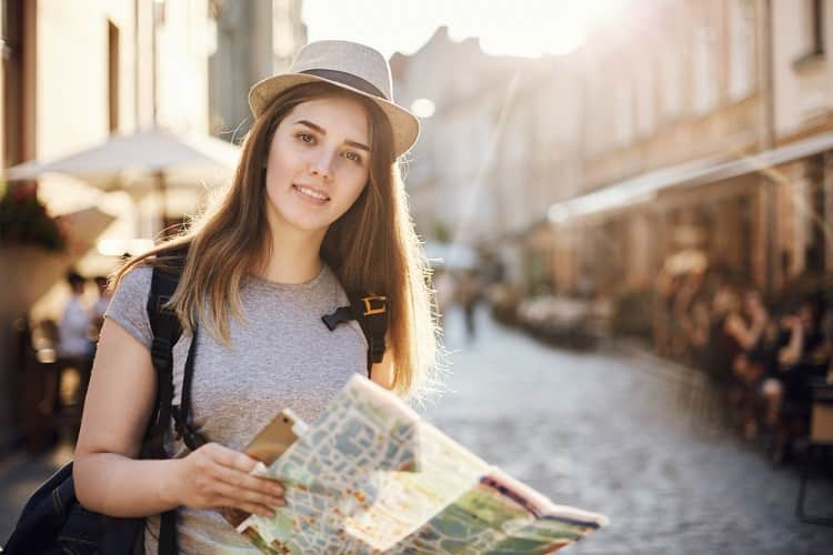portrait-of-woman-travelling-the-world-using-map-and-tablet-standing-in-small-european-city-min