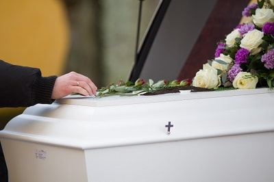 closeup-shot-of-person-hand-on-casket-with-blurred-background-min