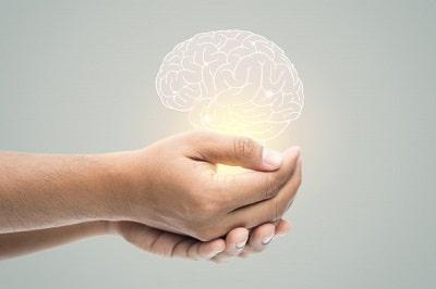 dia-salud-mental-hombre-que-sostiene-ilustracion-cerebro-pared-gris-min