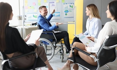 hombre-discapacitado-silla-ruedas-que-muestra-graficos-pizarra-sus-alumnos_