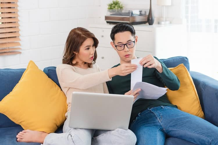serious-asian-husband-checking-analyzing-statement-utilities-bills-sitting-together-at-home-min