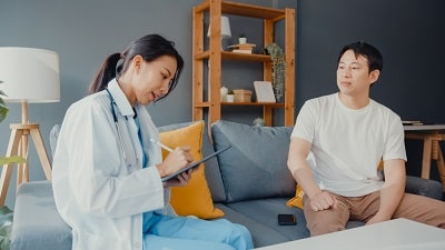 young-asia-female-professional-physician-doctor-using-digital-tablet-sharing-good-health-test-news-with-happy-male-patient-sit-on-min