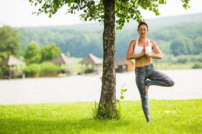 young-fit-woman-doing-yoga-in-park-near-lake-and-tree-min