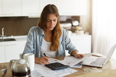 young-woman-checking-her-budget-and-doing-taxes-min